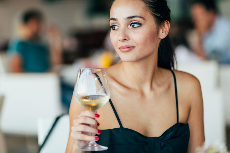 Woman dining with a glass of white wine